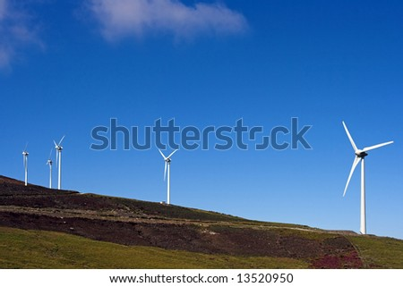 Mountain new landscape seeing wind turbines against deep blue sky - stock photo