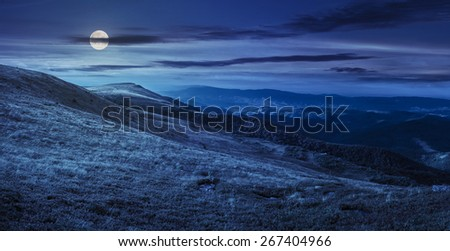 mountain panorama landscape. valley with stones in grass on top of the hillside of mountain range at night in full moon light - stock photo