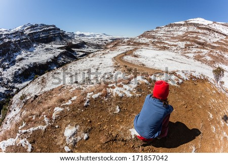 Mountain Pass Young Adventure Young unidentified girl looks down valley mountain pass covered in melting snow on a blue day. - stock photo