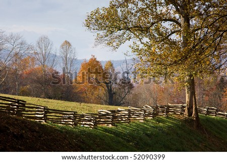 Mountain pasture with split rail wooden fence, autumn leaves. - stock photo