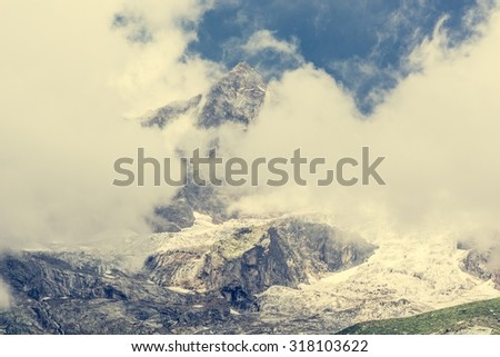 Mountain peak covered with clouds with glacier breaking under neath it.