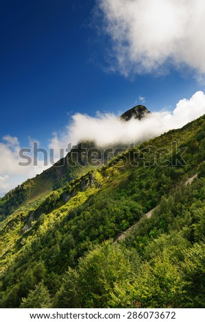 Mountain peak hidden cloud. Summer. - stock photo
