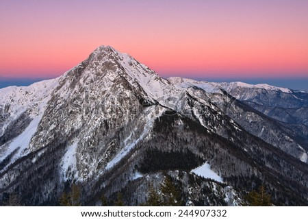Mountain peak of Storzic (2136m) in sunset lit by the last sun rays of the day - stock photo