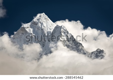 Mountain peak visible high in the sky through the clouds.