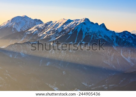 Mountain peaks of Begunjscica and Stol in sunset lit by the last sun rays of the day, Slovenia - stock photo