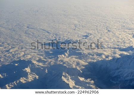 Mountain peaks rise above the cloud layer. The Alps. - stock photo