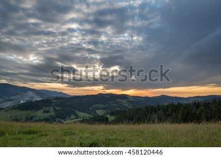 Mountain range and meadow on the background of the sunset with clouds - stock photo