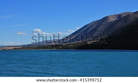 Mountain range and turquoise water of Lake Ohau. Landscaoe in New Zealand. - stock photo