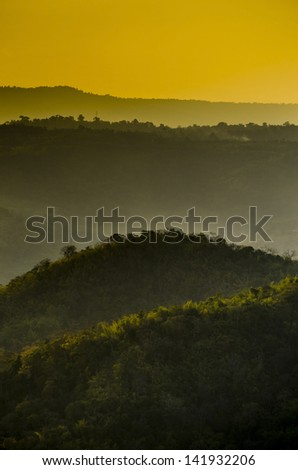 Mountain range in the rays of the rising sun - stock photo