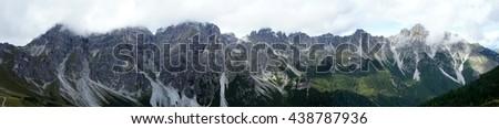 Mountain range in the Stubai Valley in Tyrol, Austria, rugged rocks, steep slopes, mountaintops partly in clouds, panoramic/Mountain range in Tyrol - stock photo