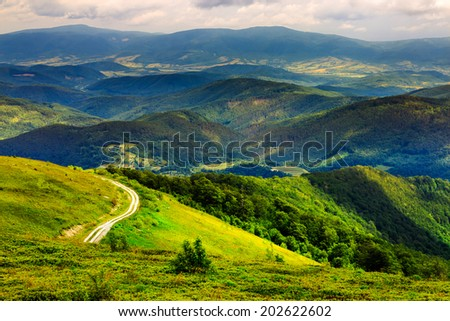 mountain range summer landscape. valley with stones and road on the hillside. forest on the mountain under the beam of light falls on a clearing at the top of the hill. - stock photo