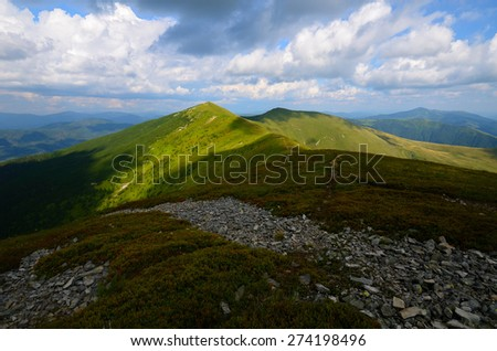 Mountain range with green grassy hills and light patches and rocks on the foreground - stock photo