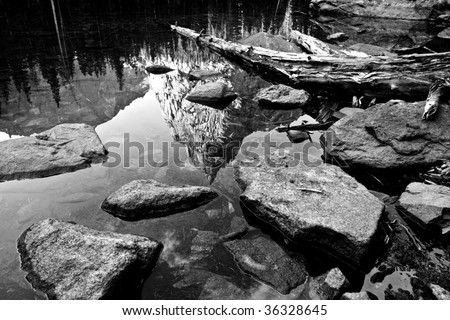 Mountain reflecting in rocky shoreline - stock photo