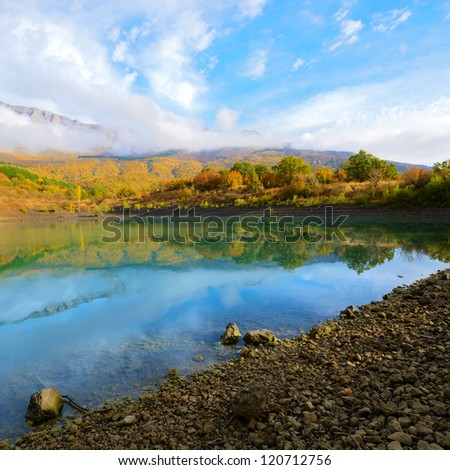 Mountain reflections in a deep quiet lake - stock photo