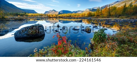Mountain ridge panorama reflected in shallow Polygonal freshwater lake with bright autumn foliage in foreground, Hibiny mountains above the Arctic Circle, Russia - stock photo