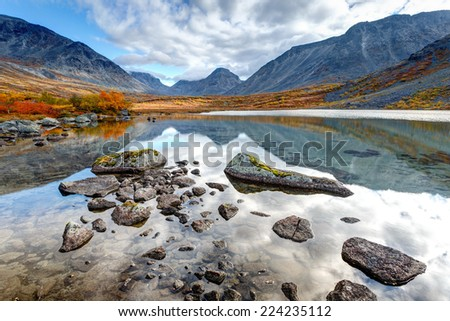 Mountain ridge reflected in Tahtarjavr freshwater lake in Malaya Belaya river valley, Hibiny mountains above the Arctic Circle, Russia