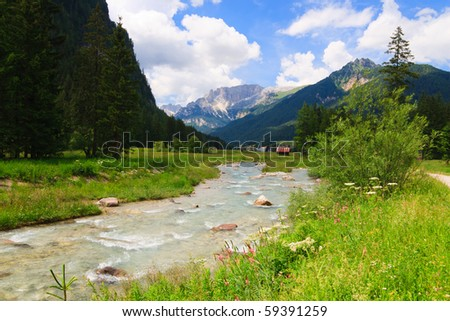 Mountain river flows through green valley in Dolomites. - stock photo