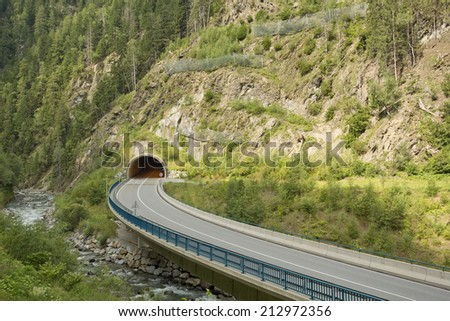 mountain road and tunnel in the Alps - stock photo