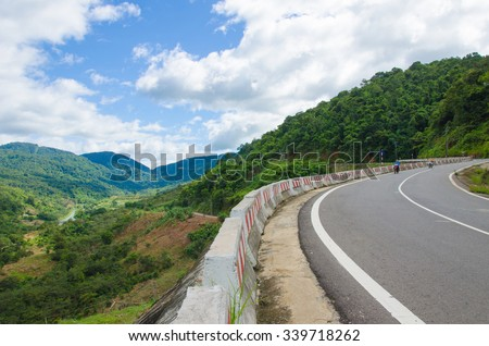 Mountain road at sunny day with clouds on the sky in Dalat highland, Vietnam