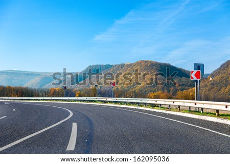 Mountain road bright autumn day with blue sky - stock photo
