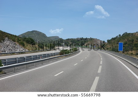 Mountain road curve with blue sky - stock photo