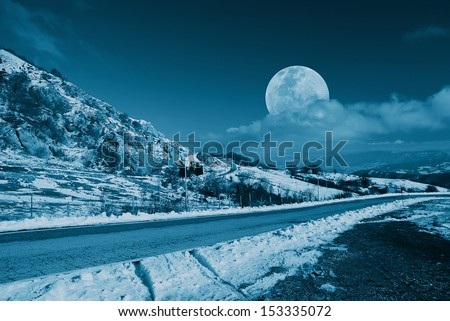 mountain road in the evening with moon in the sky - stock photo