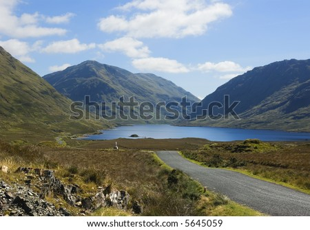 Mountain road in the west of Ireland, leading past a wayside monument erected in memory of the victims of the 1845-1846 Irish Potato Famine, who wandered through this countryside in search of food. - stock photo