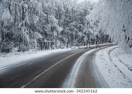Mountain road in winter snow - stock photo
