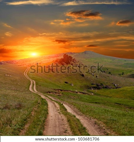 Mountain road on sunset background - stock photo