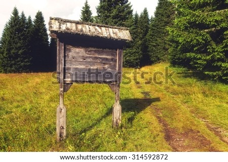 Mountain road sign,made out of wood next to hiking trail. - stock photo