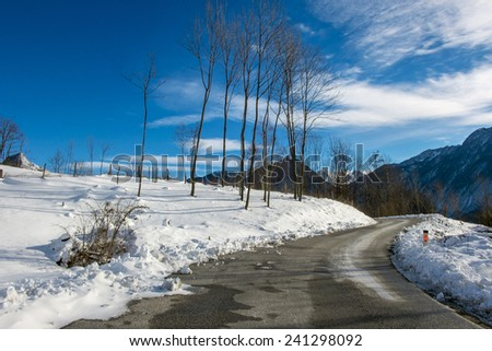 mountain road with snow under a blue sky - stock photo
