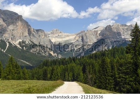 Mountain's path on the Dolomites with green forest and rocky mountains - stock photo