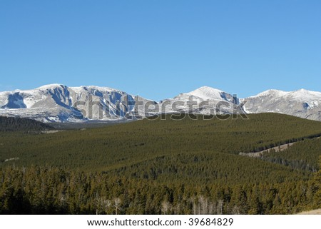 mountain scene with blue skies and wispy clouds and pine trees - stock photo
