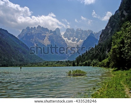 Mountain scenery in the Sexten Dolomites in South Tyrol, Italy; foreground the Lake Duerrensee and background the back side of the Three Peaks, blue sky and with white clouds/Lake in the Dolomites