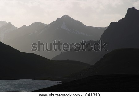 Mountain silhouette and a small house - stock photo