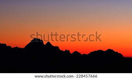 Mountain silhouette in the afterglow. View from the Gartnerkofel above Nassfeld pass, Austria - stock photo