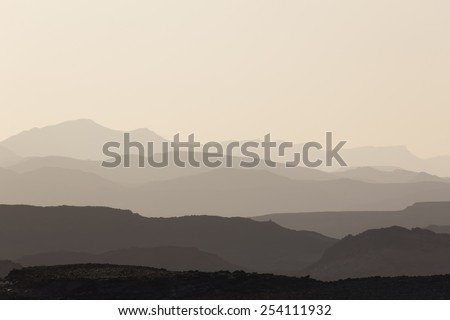 mountain silhouette in the Negev desert in Israel at sunset sunrise - stock photo