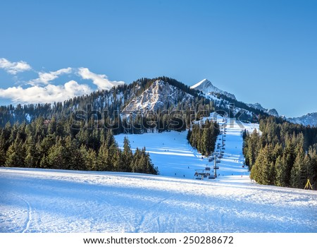 Mountain skiing slopes and ski lift at Hausberg top near Garmisch-Partenkirchen town in Bavarian Alpes in Germany with Zugspitze peak and blue sky at the backdrop on a clear winter day - stock photo