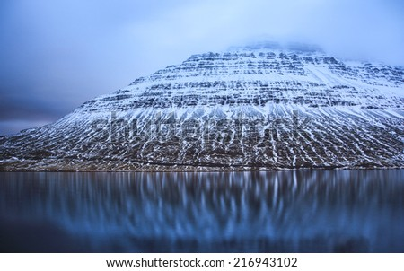Mountain slope with snow reflection in fjord water in Eskifjordur, Iceland - nature background - stock photo
