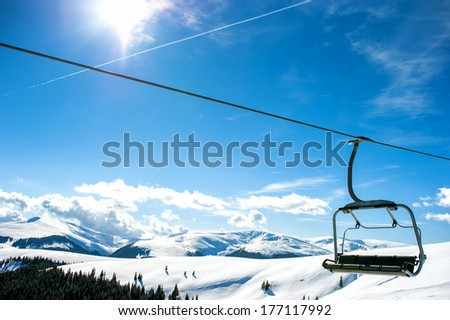 Mountain slopes with chairlift on a winter sunny day - stock photo