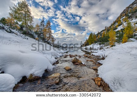 Mountain small river enters the lake in autumn with the first snow - stock photo