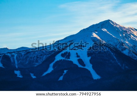 Mountain snow peak, beautiful natural winter backdrop. Ice top of the hill, blue sky background. Alpine landscape.