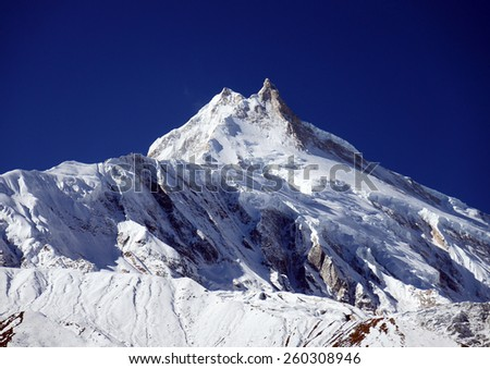 Mountain snowy peak in the blue sky