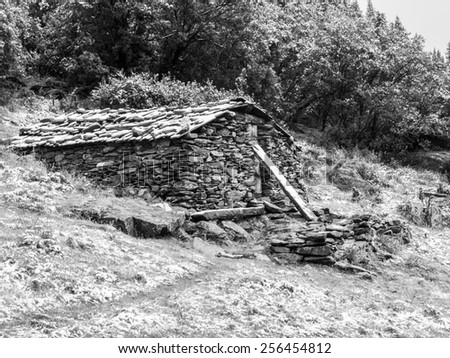 Mountain stone shelter for tourist, bivouac, Yading reserve, Daocheng, Sichuan, China, black and white image - stock photo