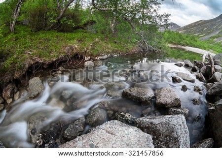 Mountain stream coming down from the tops of the mountains in Khibins, long exposure, wide angle - stock photo