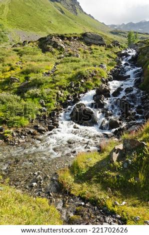 Mountain stream flows through the rocks in Alps - stock photo