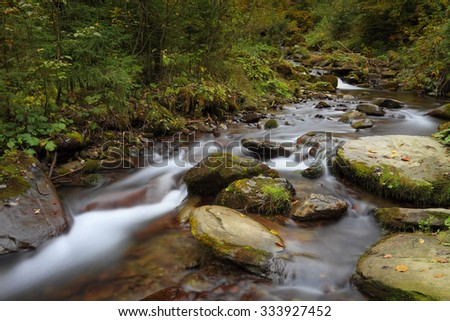 Mountain stream in a forest at autumn season. Yellow leaves on the stones - stock photo