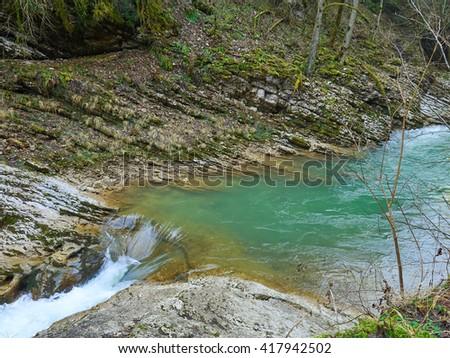 Mountain Stream in Springtime. Cascade river over mossy rocks. - stock photo