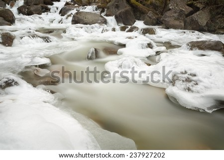 Mountain Stream, Winter Ice. Long exposure of a mountain stream with ice and snow. Motion blur.  - stock photo
