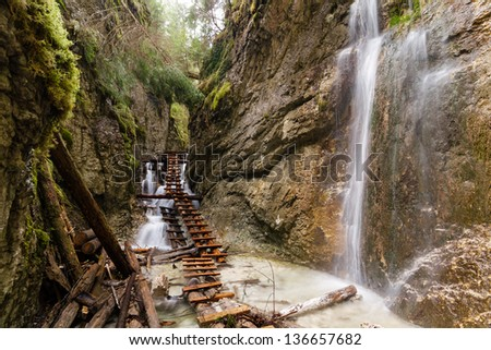 Mountain stream with ladder in canyon - stock photo